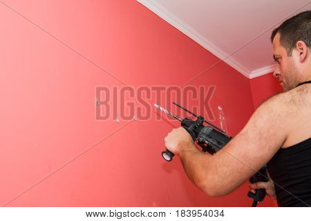 drilling the wall with Impact drill red carrot color wall