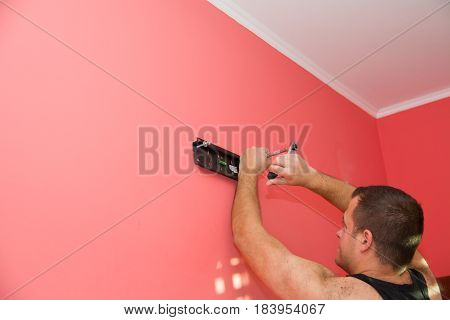 the man is installing the TV wall mount red carrot color of wall