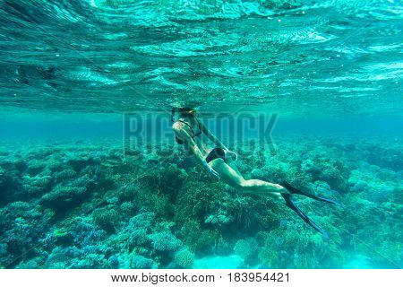 Underwater Shot Of The Young Lady Gliding Over Vivid Coral Reef On A Breath Hold In Sea Water