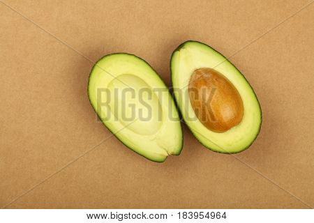 Two Halves Of Avocado On Brown Paper Parchment