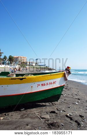 TORROX COSTA, SPAIN - OCTOBER 27, 2008 - Traditional wooden fishing boat on the beach with tourists to the rear Torrox Costa Malaga Province Andalusia Spain Western Europe, October 27, 2008.