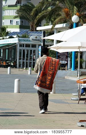 TORROX COSTA, SPAIN - OCTOBER 27, 2008 -Street seller walking along the promenade with rugs over his shoulder Torrox Costa Malaga Province Andalusia Spain Western Europe, October 27, 2008.