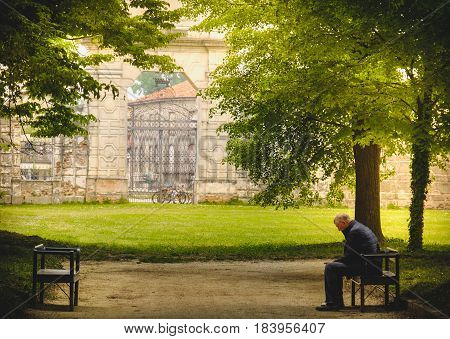 Stra, Italy 25 Apr 2017 - aged man sitting in loneliness on a park banch in the shade of trees