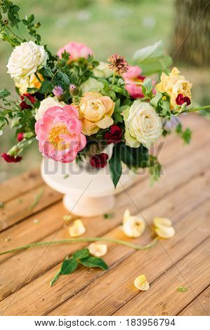 bouquet, flower, gifts and floral arrangement concept - top view on fresh bouquet of yellow and white roses, red carnations, pink charming peon, shoots of wild rose, in white vase on wooden table
