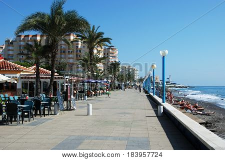 TORROX COSTA, SPAIN - OCTOBER 27, 2008 - View along the promenade with pavement cafes to the left hand side and tourists relaxing the beach to the right Torrox Costa Malaga Province Andalusia Spain Western Europe, October 27, 2008.