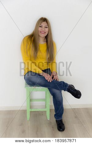 Smiling girl with long brown healthy straight hair in yellow are sitting on the stool