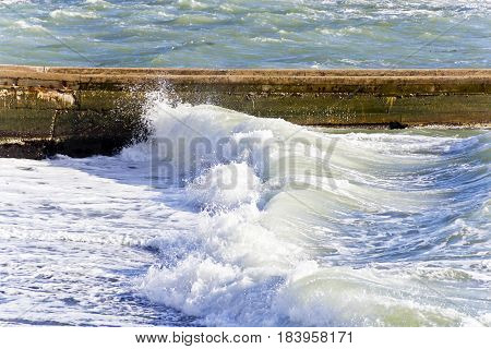 Sea waves with foam are breaking on the breakwater