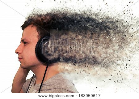 Profile of a man with headphones isolated on white. Particulate particles from the headphones
