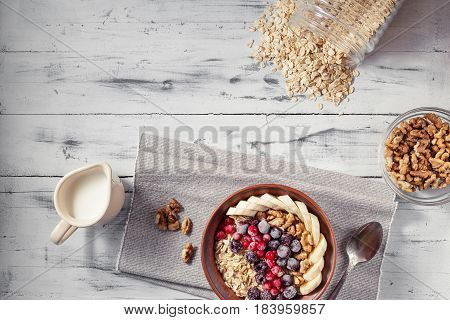 Oatmeal in brown clay bowl with frozen berries as blackcurrants, redcurrants, blackberries, bananas and walnuts ready to eat, jug with milk and spoon on the light wooden table. Top view