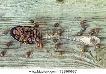 Roasted coffee beans on vintage spoon on wooden table