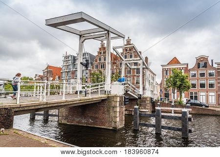 Haarlem Netherlands - August 3 2016: Picturesque landscape with beautiful traditional houses and bridge in canal of Haarlem