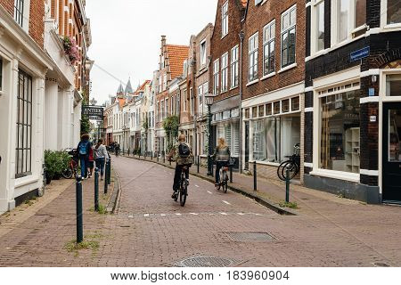 Haarlem Netherlands - August 3 2016: Cyclist riding in a picturesque street with beautiful traditional houses in Haarlem