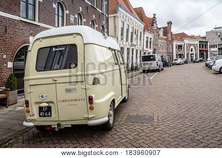 Haarlem Netherlands - August 3 2016: Picturesque street with beautiful traditional houses and retro van vehicle on foreground in Haarlem