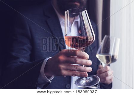 horizontal close up of a Caucasian man with beard black suit and white shirt offering a tall glass of rose wine at an event by the window natural light