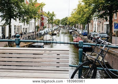 Haarlem Netherlands - August 3 2016: Picturesque cityscape with beautiful traditional houses and vessels in canal of Haarlem