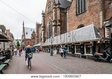 Haarlem Netherlands - August 3 2016: Picturesque cityscape of Haarlem with the cathedral a woman riding a bicycle and tourists