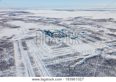 Oil and gas industry. Oil pump jack station in a oil field in tundra. Petrochemical object in West Siberia.