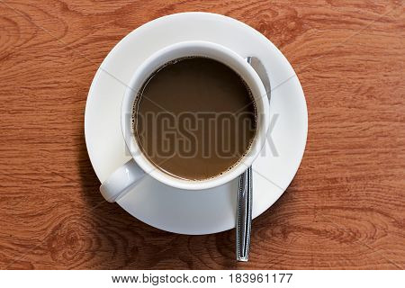 Coffee in white cup on wooden floor