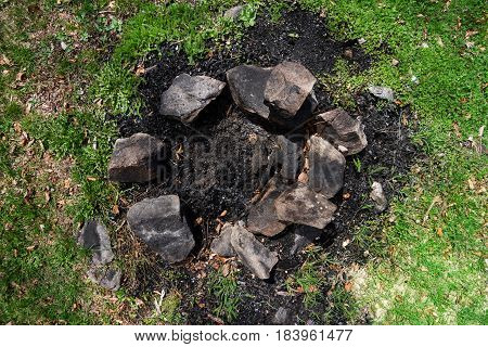 top view of extinguished campfire place with grass stones and black ashes