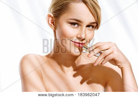 Young blonde model applying lipstick. Photo of girl with perfect make up on white background. Beauty concept