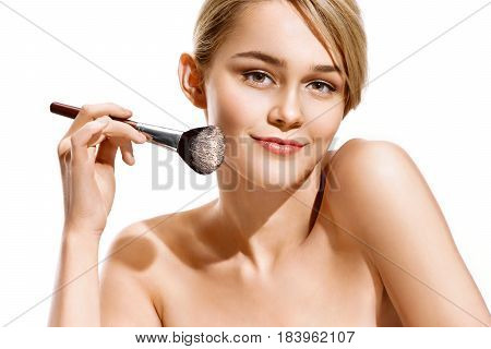 Smiling beautiful woman with make up brush near her face. Photo of attractive woman isolated on white background. Youth and skin care concept