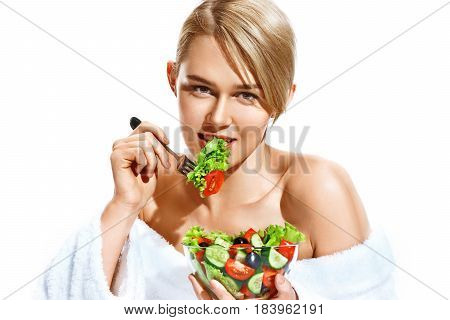 Attractive woman eating healthy vegetable salad from transparent crockery. Photo of blonde woman isolated on white background. Healthy lifestyle