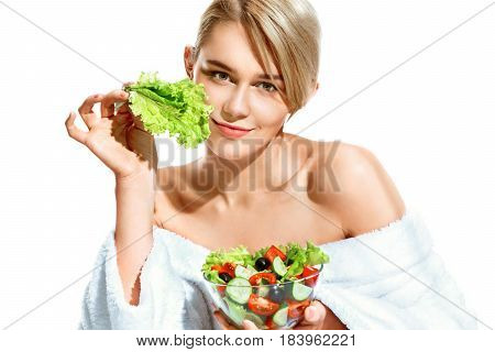 Charming young woman with lettuce leaf. Photo of smiling blonde in bathrobe holding vegetable salad isolated on white background. Healthy lifestyle