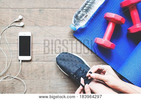 Overhead view of woman in black sneaker with smartphone and sport equipment on wood floor