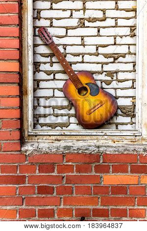 Acoustic guitar on red and white brick background with copy space