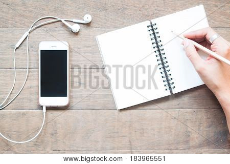 Overhead view of smartphone with empty notebook and woman holding pencil