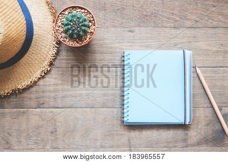 Blue color empty notebook with cactus and hat on wood table Lifestyle concept