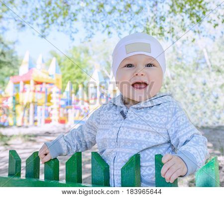 A small child smiles directly into the frame. In the background a children's Playground town castle