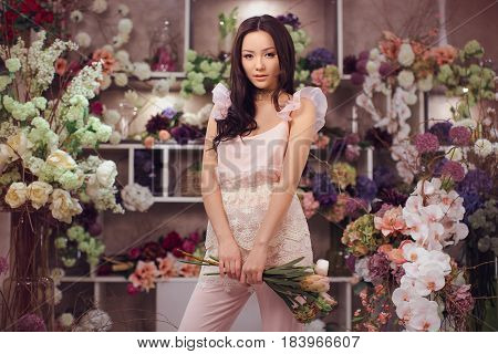 Florist. Girl and bouquet flowers peonies in hands. Woman standing against floral bokeh background in flower shop. Joyful asian female. Playful fashion model looking at camera and smiling.