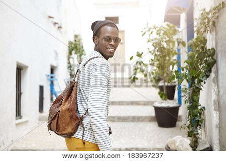 Picture Of Happy Young African Man In Shades, Yellow Pants And Striped White Shirt With Backpack Sta