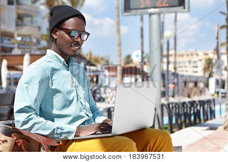 Attractive Cheerful Young African American Male Freelancer Dressed In Stylish Wear Sitting On Urban