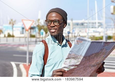 Here It Is. Joyful African American Backpacker Holding Paper Map In His Hands While Sightseeing In R