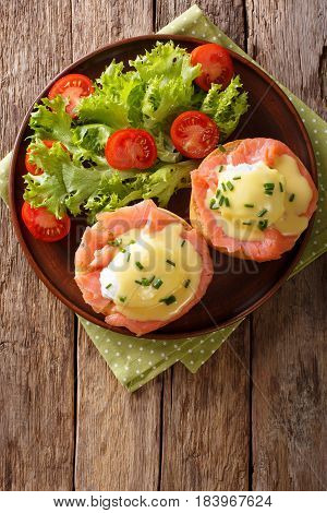 Hearty Breakfast: Poached Eggs With Salmon And Hollandaise Sauce Close-up. Vertical Top View