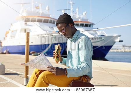Outdoor Shot Of Trendy Looking Hungry Young Afro American Male Traveler Studying City Guide In His H