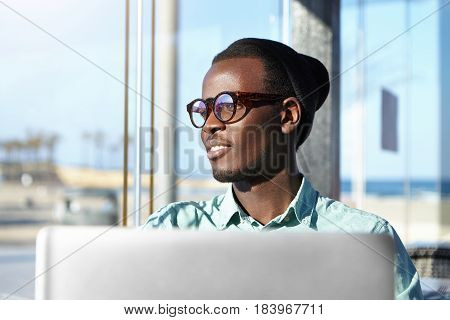 Attractive Joyful Young African Male Wearing Stylish Clothing Sitting In Front Of Laptop Computer Wh