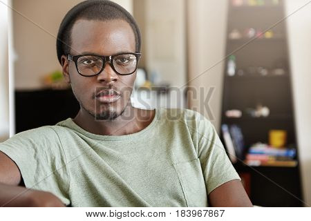 Indoor Shot Of Attractive Young African American Man Wearing Trendy Black Glasses And Hat Spending W