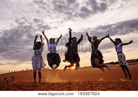 MUI NE VIETNAM - MARCH 24 2017. A group of young women jumps on the edge of a sand dune with the sun set in the background. Backlit in backlight. Silhouettes of jumping women. Sand dune at Mui Ne Vietnam