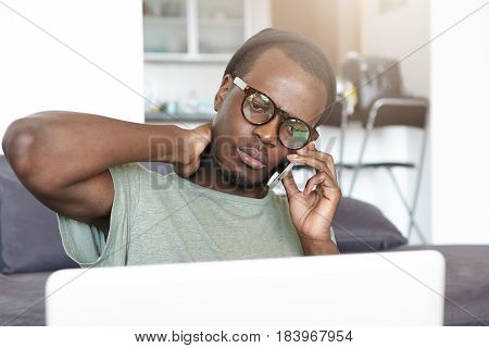 Worried Young African Man In Stylish Glasses And Hat Looking Serious And Sad, Rubbing His Neck While