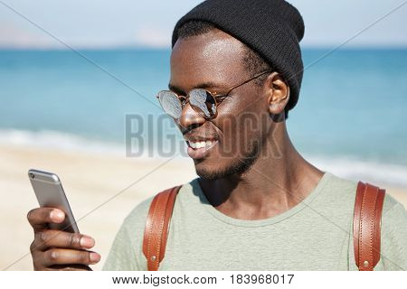 Trendy Looking Young Dark-skinned Hipster In Mirrored Lens Shades And Headwear Reading Message Or Br