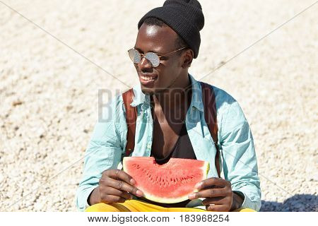 Fashionable Dark-skinned Young European Male Student In Stylish Sunglasses And Headwear Relaxing On