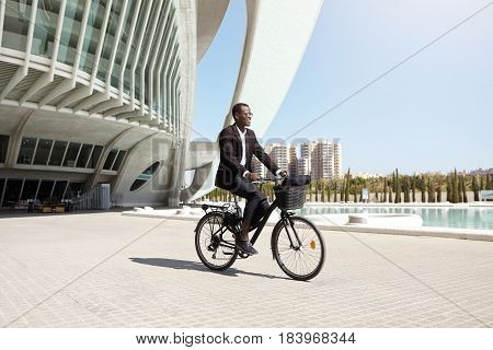 Confident Eco Friendly Dark-skinned Ceo Using Two Wheeled Pedal Assist Vehicle To Get To Work. Succe