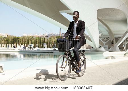 Joyful Environmentally Conscious African Office Worker Wearing Black Formal Suit And Stylish Shades