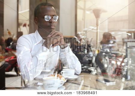 Confident Thoughtful Young African American Businessman In Stylish Eyewear Clasping Hands While Sitt