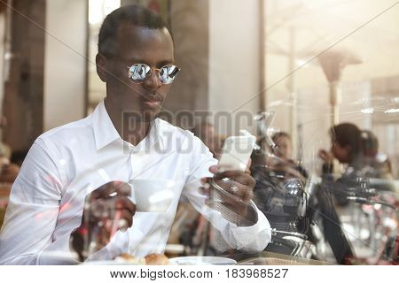 Staying Connected. View Through Window Glass Of Handsome Black European Employee In Shades And Forma