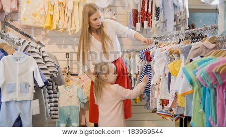 Blonde young woman with little daughter chooses kids dress in clothes store, telephoto