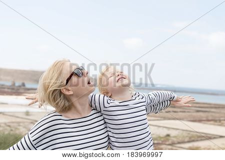 Happy Lady And Young Girl In Matching Clothes Looking Up